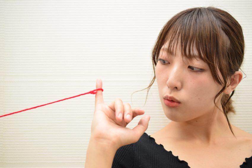 女性の小指から赤い糸が伸びている