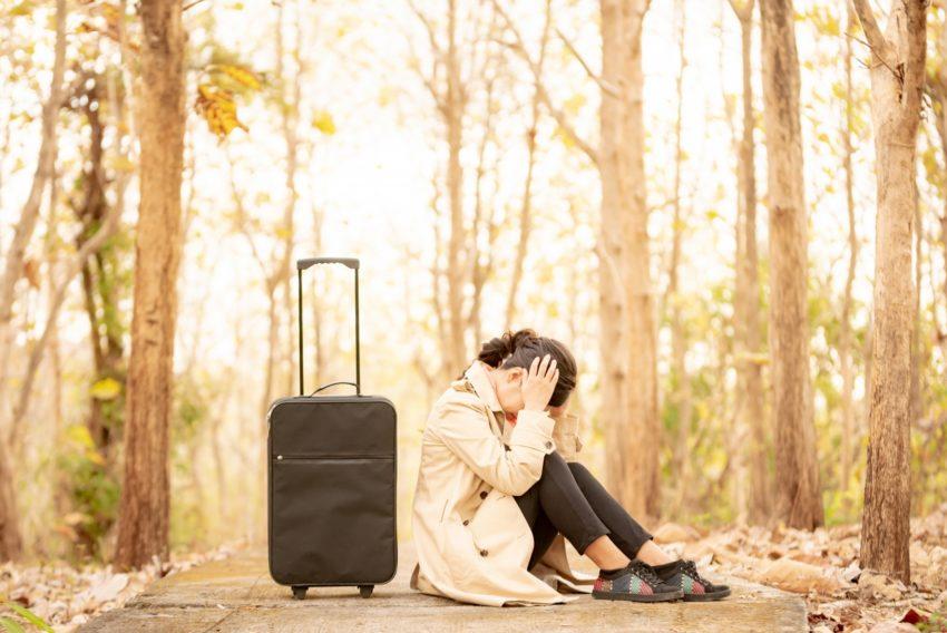 スーツケースの前で頭を抱える女性