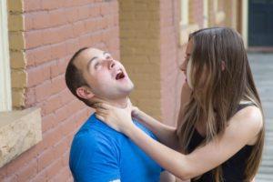 女性が男性の首を絞めている